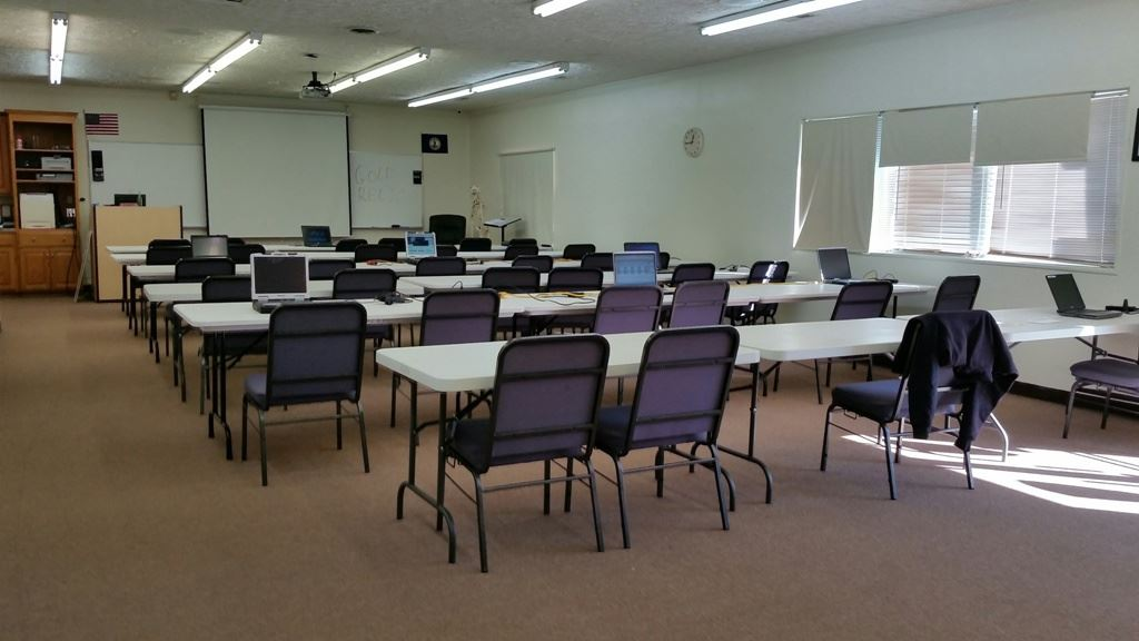 Classroom with Rows of Tables Facing Projector Screen